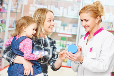 mother carrying her daughter and female pharmacist reading the label of the medicine while smiling