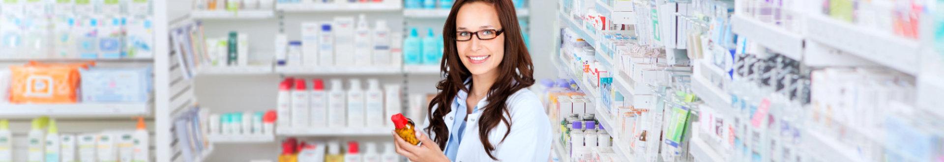 female pharmacist smiling while holding medicine