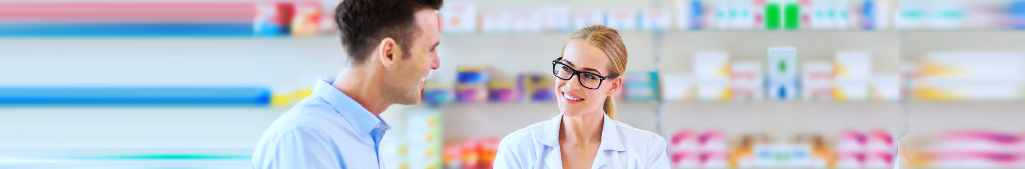 male customer and female pharmacist smiling while looking at each other